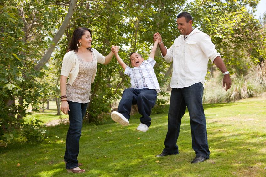 Hispanic Man, Woman and Child having fun in the park.